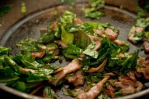 Frying the bacon and spring greens