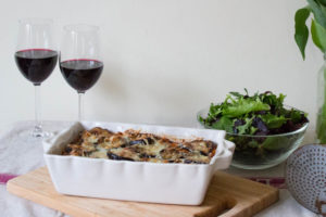 Layered Ragu and Aubergine Pasta Bake with salad and wine