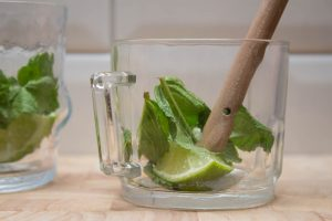 bashing the lime and mint together for mojitos