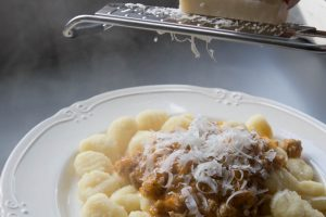 Adding Parmesan to sausage ragu and gnocchi